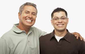 Hispanic father and adult son hugging